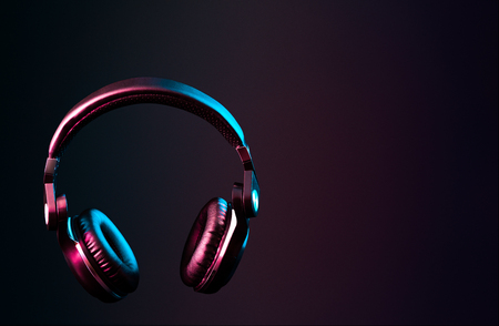 Headphones with pink & blue colored lighting, futuristic lifestyle/music image with copy space. Stock Photo