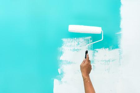 Mujer pintando sobre una pared de color turquesa con rodillo de pintura.