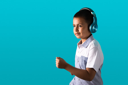 Small boy listening to music on wireless headphones smiling and dancing with blue background and copy space for text.