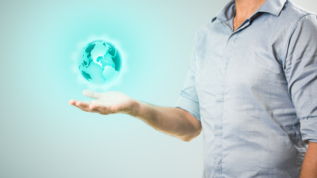 Casualy dressed businessman holding virtual projection of the world in his hand Reklamní fotografie