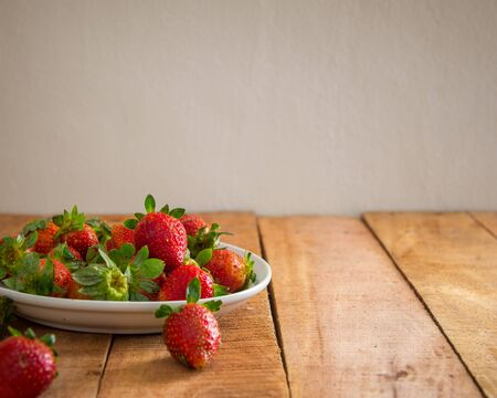 Ripe red strawberries on wooden table with copy space for text. Simple healthy food concept. Reklamní fotografie