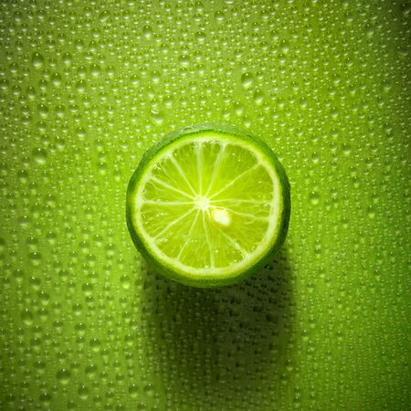 Slice of lime on green background with water droplets creating texture - fresh and healthy food concept image