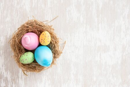 Easter eggs in nest on simple white wash wood tabletop - flat lay easter concept image with copy space for text.