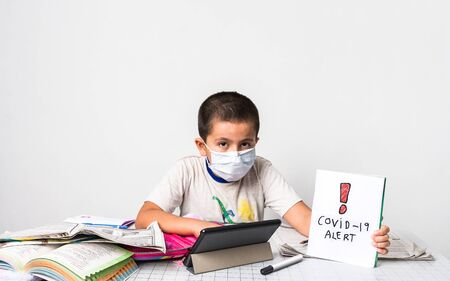 Corona Virus / home schooling concept image with a young boy wearing a mask sitting at a table studying - health care and education concept image with copy space for text.