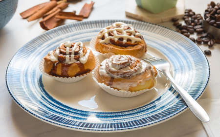 Cinnamon rolls, freshly baked on a plate kitchen tabletop - Baking and home cooking concept image.