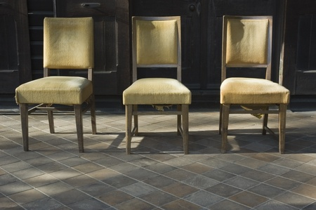 three old chairs lined up outside lit by sunlight