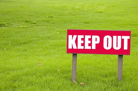 Keep out sign on green grass photo