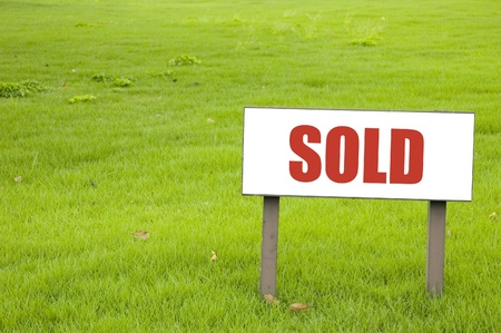 sold sign on green grass photo