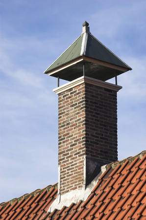 pitched: Chimney over a red tiled roof