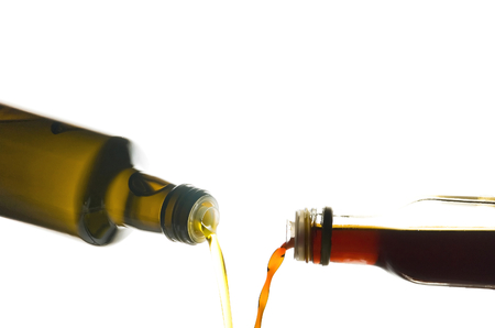 poured: Olive oil and vinegar being poured from bottles isolated on white