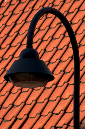 pitched roof: Street lamp next to a red tiled roof