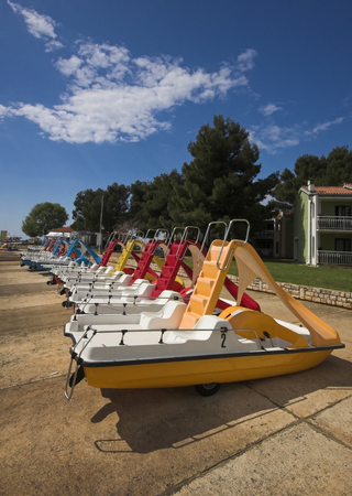 Water bicycles rowed at the edge of a sea photo