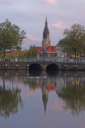 countless: Delft - cathedral tower overlooking the countless canals and bridges of this small Dutch town known to the locals as small Amsterdam. Holland is a country where majestic medieval architecture seems literally to grow out of water. Stock Photo