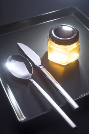 Yellow jar on a black plate with silver cutlery