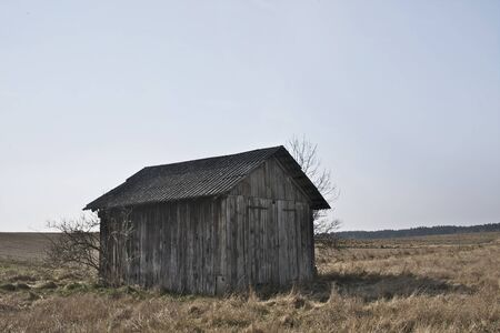 old wooden shed standing in the middle of a hayfield, in early Spring