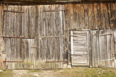 barn wall with doors, made of old wooden planks in early Spring