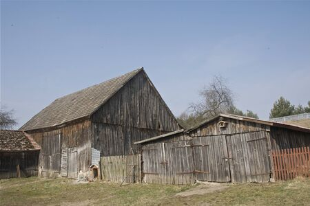 Old farm in early Spring under a clear blue sky, rural wooden architecture