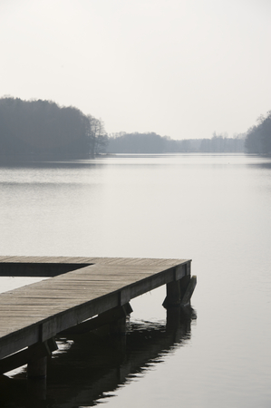 Wooden pier on a Polish lake on an early spring morning