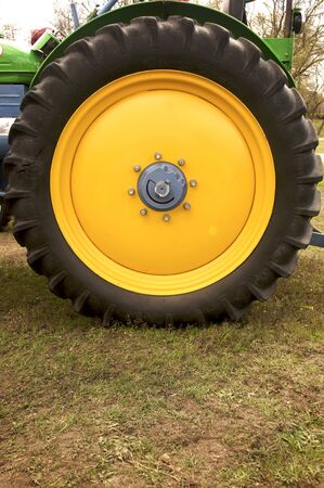 Closeup of a huge yellow wheel of a retro tractor