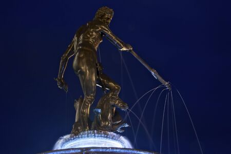 Statue of Neptune decorating the Old Square of Gdansk in Poland at night. Sightseeing and touristic attraction