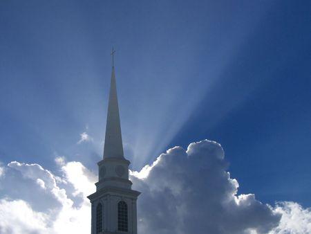 church steeple: Un campanile e la chiesa con i raggi di sole in tutta illuminata da dietro una nuvola