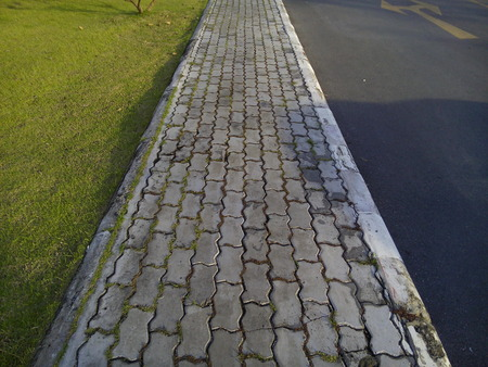 Concrete brick footpath in the city park. Imagens