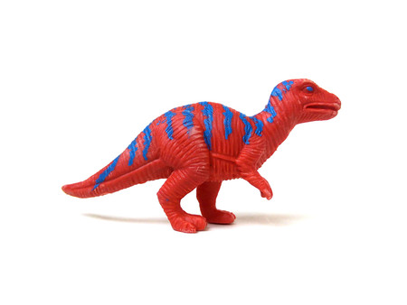 Close up of red t-rex dinosaur toy isolated on white background.