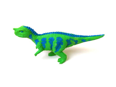Close up of green dinosaur toy isolated on white background.