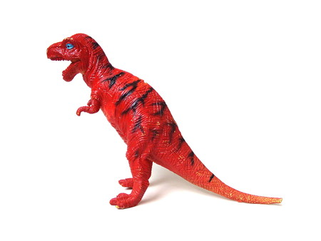 Close up of red tyrannosaurus rex dinosaur toy isolated on white background.