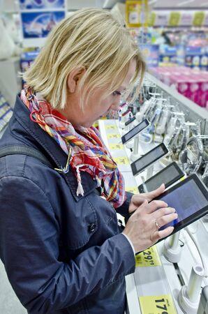 electronics store: Donna in cerca di un tablet pc in un negozio di elettronica