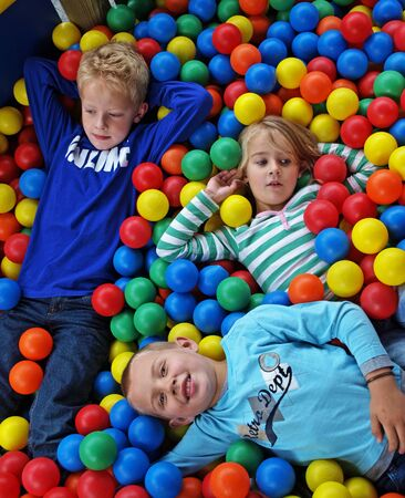 among: Young boys and a girl in colorful balls