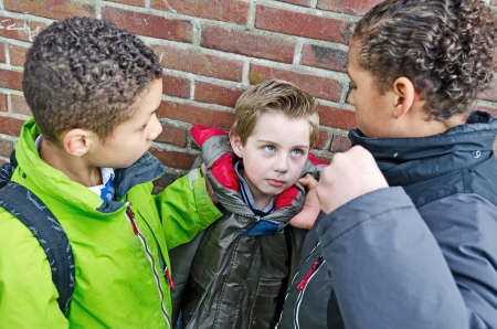 Two boys bullying little kid photo