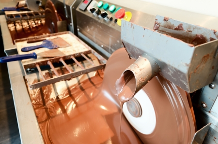 melted chocolate: Chocolate machine pouring melted chocolate