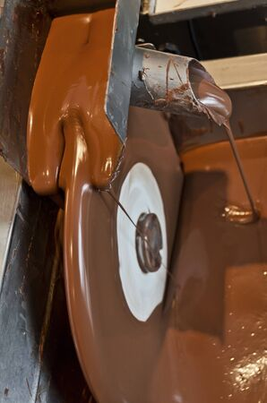 milk production: Chocolate machine pouring melted chocolate