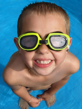 kids swimming: Boy in swimmingpool with goggles Stock Photo