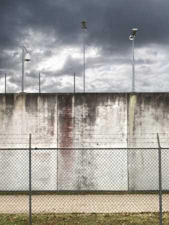 prisoner of war: Prison wall   military area with barbwired fence and security lights Stock Photo