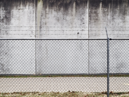 A barbed wired fence and concrete wall