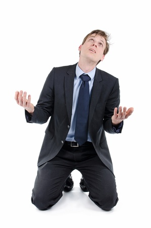 Stressed businessman on his knees begging for help photo