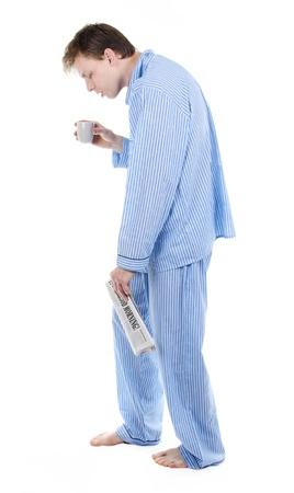 insomnio: Hombre muy cansado en pijama s con el peri�dico y el caf� Foto de archivo