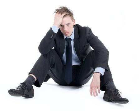derrumbe: Hombre de negocios deprimido sentado en el suelo con las manos en su pelo