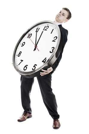 Businessman carrying heavy clock
