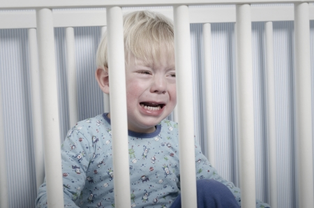 Crying boy in bed or crib does not want to go to sleep photo