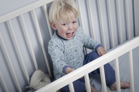 Crying boy in bed or crib does not want to go to sleep