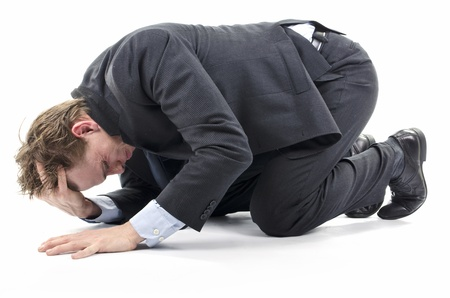 Depressed businessman on knees on the floor face down