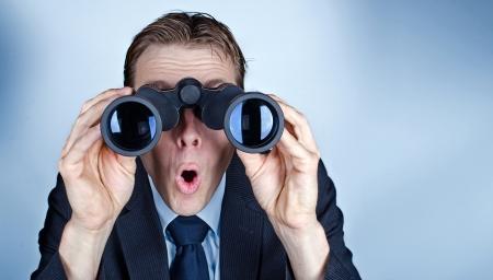 Businessman looking through field glasses or binoculars and looking worried