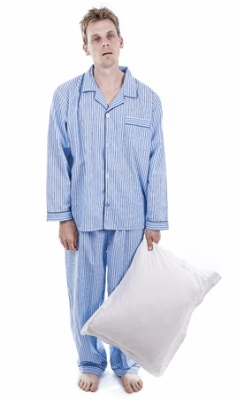 Exhausted man in blue pajamas holding pillow