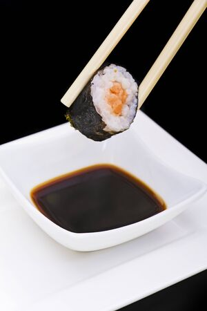 Sushi with chopsticks dip in sauce photo