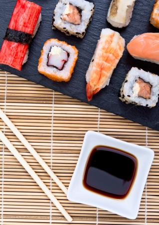 Sushi with chopsticks on black plate with sauce Stock Photo - 20875727