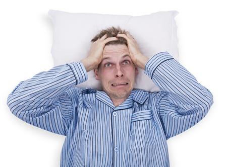 desorden: El hombre en la cama preocupado o estresado con pijama de rayas