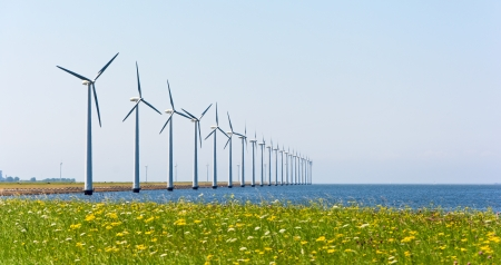 Wind energy windmills near grassland and sea shore photo